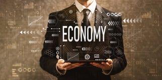 Econom?a con el hombre de negocios que sostiene una tableta foto de archivo
