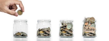 Economia do dinheiro, mão que põe a moeda no frasco de vidro com as moedas dentro de crescer acima, sobre o fundo branco, o conce fotografia de stock