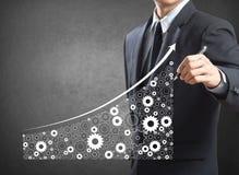 Economia ed industria crescenti del disegno dell'uomo di affari rappresentate dagli ingranaggi Fotografia Stock