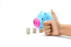 Economia, mão masculina que põr uma moeda no banco piggy Imagem de Stock