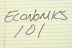 Economia 101 su un blocco note giallo Immagini Stock Libere da Diritti