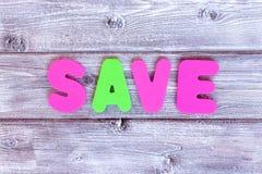 Economias da mensagem feitas de letras coloridas no fundo de madeira rústico do vintage imagens de stock royalty free