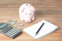 Economias home, conceito do orçamento Casa, bloco de notas, pena, calculadora e moedas modelo na tabela de madeira da mesa de esc Imagem de Stock