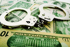 Economic. Silver handcuff and dollar bank notes Royalty Free Stock Photos