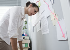Economic breakdown. Female office worker bent over with head lening to a wall and negative business chart Stock Photos