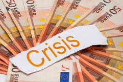Economic crisis. Word Crisis printed on a piece of paper and placed above the pile of 50 euro banknotes Royalty Free Stock Image