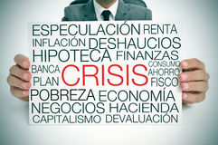 Economic crisis, in spanish. A businessman holding a signboard with different terms in spanish related to the economic crisis concept Royalty Free Stock Photography