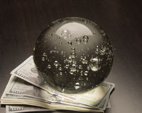 Economic Forecast. Crystal ball and money on a black background Stock Photos