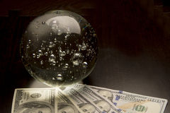 Economic Forecast. Crystal ball and money on a black background Stock Photography