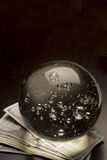 Economic Forecast. Crystal ball and money on a black background Stock Images