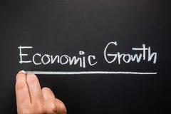 Economic Growth. Hand writing Economic Growth topic on chalkboard stock photos