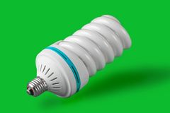 Economic light bulb standing on green background Stock Images