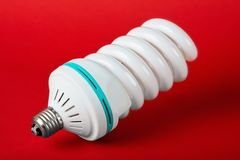 Economic light bulb standing on red background Royalty Free Stock Images