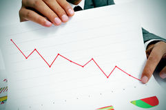 Economic losses. Man wearing a suit sitting in a table showing a graph of economic losses Royalty Free Stock Photos