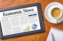 Economic News. Tablet on a desk - Economic News Royalty Free Stock Photography