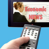 Economic news on tv. Close up of a remote control watching economic news on tv royalty free stock photography