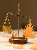 Economic prognosis on autumn. The scales with golden coins and autumn lives Royalty Free Stock Photo