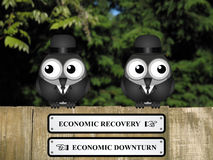 Economic Recovery or Downturn. Comical economic recovery and economic downturn signs with businessmen birds perched on a timber garden fence against a foliage Royalty Free Stock Photos