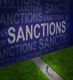Economic Sanctions. As a global economy symbol for problems with political disputes affecting trade as a man standing in front of a brick wall with words as a Stock Photos