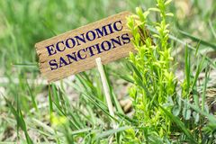 Economic sanctions wooden sign. Economic sanctions on wooden sign in garden with flower stock images