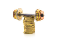 ECONOMIC STRENGTH 2. A pile of coins with a coin-weight-lift on top of it Royalty Free Stock Image