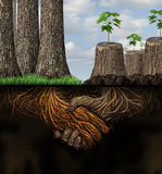 Economic Support. And financial assistance business concept as a forest of healthy trees helping a group of chopped tree trunks as roots shaped with a handshake Stock Photos