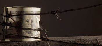 Economic warfare, sanctions and embargo busting concept. US Dollar money wrapped in barbed wire