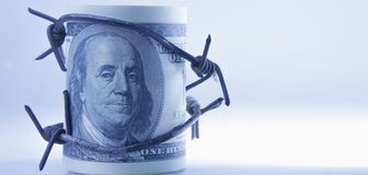 US Dollar money wrapped in barbed wire as symbol of economic war