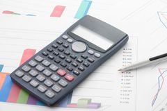 Economical analyses. A bar graphs and calculator and pen on it Royalty Free Stock Photography