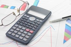 Economical analyses. A bar graphs and calculator, pen, glasses on it Royalty Free Stock Photos