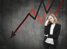 Economical crisis is bad for you. Business woman standing near blackboard with arrows going down. Concept of decline and economical crisis Royalty Free Stock Image