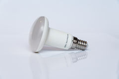 Economical lamp. LED lamp lies on a white surface.Copy space Stock Photos