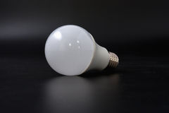 Economical light bulb on a black background. Royalty Free Stock Photos