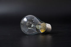 Economical light bulb on a black background. Stock Photos