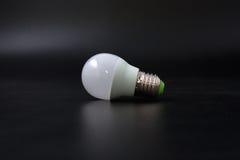 Economical light bulb on a black background. Stock Photography
