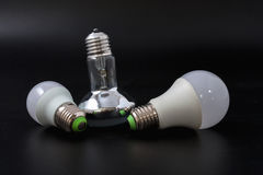 Economical light bulb on a black background. Royalty Free Stock Images
