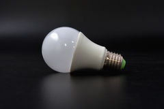 Economical light bulb on a black background. Stock Images