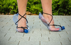 Economical wife showing homemade plastic bottle sandals Stock Photos