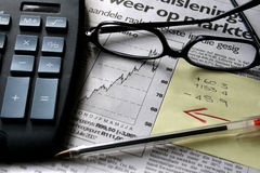 Economics. Business paper with calculator, spectacles, pen and post-it notes Stock Photography