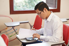 Economics education. Vietnamese adult student making calculations in the class royalty free stock image