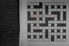 Economie en winsten in rood als oplossingen aan een krantenkruiswoordraadsel dat wordt geschreven stock foto's