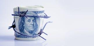 Economische oorlogvoering en embargo busting concept Amerikaanse dollargeld in prikkeldraad wordt verpakt dat stock afbeeldingen