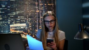 Economista fêmea novo que verifica o relatório e que chama ao colega para a consulta vídeos de arquivo