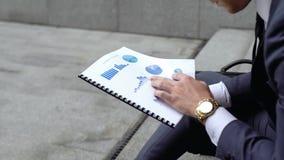 Economista que analiza gráficos y cartas antes de la reunión importante, comparando datos fotografía de archivo libre de regalías