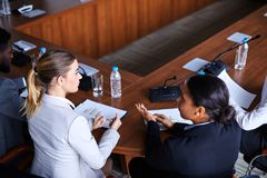 Economists at conference. Two young female analysts or economists discussing financial issues before conference while sitting by table royalty free stock image