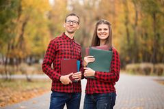 Economists couple decide start business together. Friends finally graduated from university. Handsome guy and beautiful girl in red shirt ready to overcome royalty free stock photos
