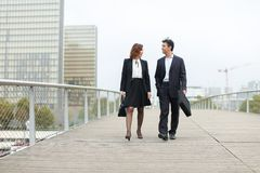 Economists male and female in strict suits walking. Economists walk during lunch break, married American middle-aged couple going to have snack. Man and women royalty free stock photos