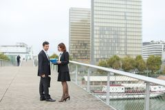 Economists male and female in strict suits walking. Economists walk during lunch break, married American middle-aged couple going to have snack. Man and women royalty free stock photography