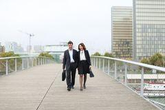 Economists male and female in strict suits walking. Economists walk during lunch break, married American middle-aged couple going to have snack. Man and women royalty free stock image