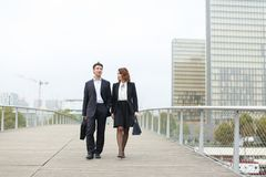 Economists male and female in strict suits walking. Economists walk during lunch break, married American middle-aged couple going to have snack. Man and women royalty free stock images